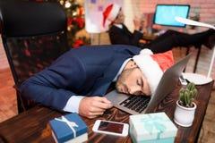 Hombre de negocios que trabaja en el ` s Eve del Año Nuevo Él estaba muy cansado y se cayó dormido detrás de su ordenador portáti Fotos de archivo libres de regalías