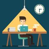 Hombre de negocios que trabaja en horas extras de última hora en oficina Imágenes de archivo libres de regalías