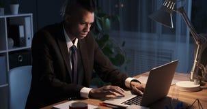 Hombre de negocios que trabaja en horas extras en oficina almacen de metraje de vídeo