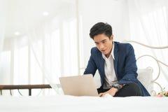 Hombre de negocios que trabaja en la cama con el ordenador portátil Fotografía de archivo