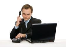 Hombre de negocios que trabaja en la computadora portátil. Aislado en blanco. Foto de archivo
