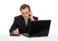 Hombre de negocios que trabaja en la computadora portátil. Aislado en blanco. Imagen de archivo