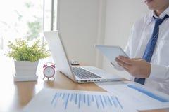 Hombre de negocios que trabaja en la oficina con el dat del ordenador portátil, de la tableta y del gráfico Imagenes de archivo