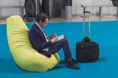 Hombre de negocios que trabaja en la tableta en el pedazo 2015, intercambio internacional del turismo en Milán, Italia Fotos de archivo