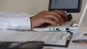 Hombre de negocios que trabaja en las cartas y los gráficos que mecanografían en datos sobre su ordenador portátil almacen de metraje de vídeo