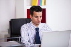 Hombre de negocios que trabaja en su ordenador portátil imagenes de archivo