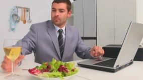 Hombre de negocios que trabaja en su ordenador portátil en el tiempo del almuerzo almacen de video