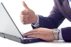 Hombre de negocios que trabaja en un ordenador con su pulgar para arriba Foto de archivo libre de regalías