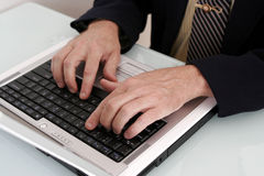 Hombre de negocios que trabaja en un ordenador portátil Fotos de archivo