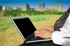 Hombre de negocios que trabaja en una computadora portátil al aire libre Fotos de archivo libres de regalías