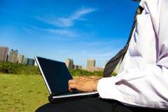 Hombre de negocios que trabaja en una computadora portátil al aire libre Foto de archivo