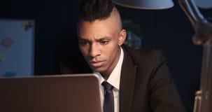 Hombre de negocios que trabaja un ordenador portátil tarde en noche
