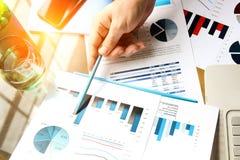 Hombre de negocios que trabaja y que analiza figuras financieras en gráficos en un ordenador portátil Imagen de archivo
