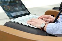 Hombre de negocios que trabaja y que analiza figuras financieras en gráficos en un ordenador portátil afuera Fotos de archivo