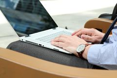 Hombre de negocios que trabaja y que analiza figuras financieras en gráficos en un ordenador portátil afuera Foto de archivo libre de regalías