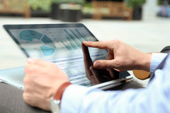 Hombre de negocios que trabaja y que analiza figuras financieras en gráficos en un ordenador portátil afuera Imagenes de archivo