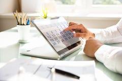 Hombre de negocios que usa el calendario en el ordenador portátil foto de archivo libre de regalías