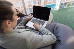 Hombre de negocios que usa el centro de Sit Panoramic Window Businessman In Coworking del ordenador portátil foto de archivo libre de regalías