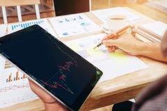 Hombre de negocios que usa el informat de trabajo del intercambio del mercado de acción de la tableta fotografía de archivo libre de regalías