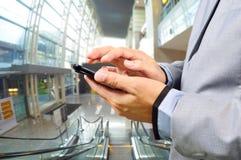 Hombre de negocios que usa el móvil mientras que va abajo de la escalera móvil Imagenes de archivo