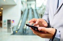 Hombre de negocios que usa el móvil mientras que va abajo de la escalera móvil Fotos de archivo libres de regalías