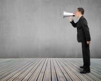 Hombre de negocios que usa el megáfono que grita con el muro de cemento f de madera Imágenes de archivo libres de regalías