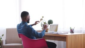 Hombre de negocios que usa el ordenador portátil e inclinándose detrás en silla de la oficina metrajes