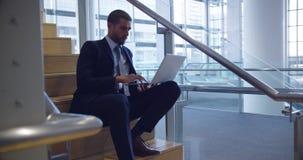 Hombre de negocios que usa el ordenador portátil en las escaleras en la oficina 4k almacen de metraje de vídeo