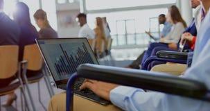 Hombre de negocios que usa el ordenador portátil en el seminario 4k del negocio metrajes