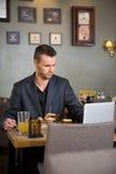 Hombre de negocios que usa el ordenador portátil mientras que comiendo el bocadillo Imagenes de archivo