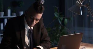 Hombre de negocios que usa el ordenador portátil y tomando notas en la oficina de la noche
