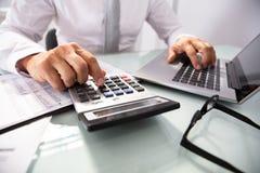 Hombre de negocios que usa el ordenador port?til y la calculadora foto de archivo libre de regalías