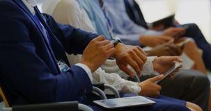 Hombre de negocios que usa el smartwatch en el seminario 4k del negocio almacen de metraje de vídeo