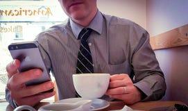 Hombre de negocios que usa el teléfono elegante para trabajar a través de hora de la almuerzo Imágenes de archivo libres de regalías