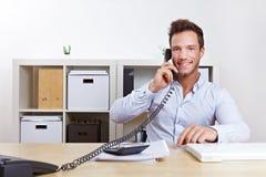 Hombre de negocios que usa el teléfono en oficina fotografía de archivo libre de regalías