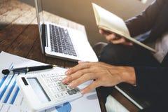 Hombre de negocios que usa la calculadora que analiza en beneficios de la compañía en una oficina moderna imagen de archivo
