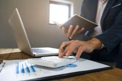 Hombre de negocios que usa la calculadora que analiza en beneficios de la compañía en una oficina moderna imagenes de archivo