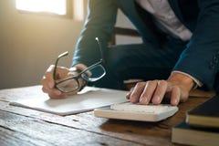Hombre de negocios que usa la calculadora que analiza en beneficios de la compañía en una oficina moderna fotos de archivo libres de regalías