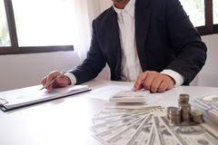 Hombre de negocios que usa la calculadora con las monedas y el dinero sobre el escritorio fotografía de archivo libre de regalías