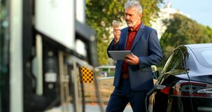 Hombre de negocios que usa la tableta digital mientras que habla en el tel?fono m?vil en la estaci?n de carga 4k metrajes