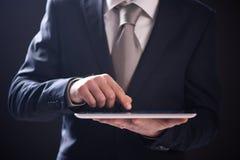 Hombre de negocios que usa la tablilla de la pantalla táctil foto de archivo libre de regalías