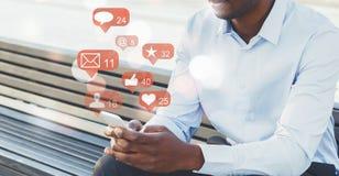 Hombre de negocios que usa medios sociales con los iconos de la notificación imagen de archivo