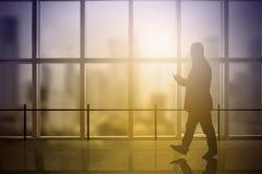 Hombre de negocios que usa un móvil mientras que camina un pasillo del edificio de oficinas Llamarada de Sun espacio vacío de la  Imagenes de archivo