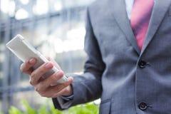 Hombre de negocios que usa un teléfono móvil y un x28; foco en el cellphone& x29; imagenes de archivo