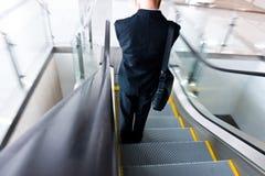 Hombre de negocios que va abajo de la escalera móvil Foto de archivo