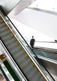 Hombre de negocios que va abajo de la escalera móvil Fotos de archivo libres de regalías