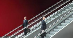 Hombre de negocios que va arriba y abajo de las escaleras móviles, concepto de éxito Foto de archivo libre de regalías
