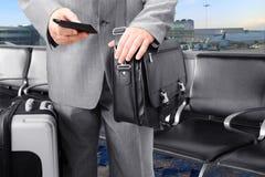 Hombre de negocios que viaja que llama por Phone en el airp Imágenes de archivo libres de regalías