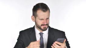 Hombre de negocios Reacting de la barba a la pérdida mientras que usando Smartphone metrajes