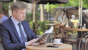 Hombre de negocios Reading Book mientras que se sienta en café al aire libre almacen de metraje de vídeo